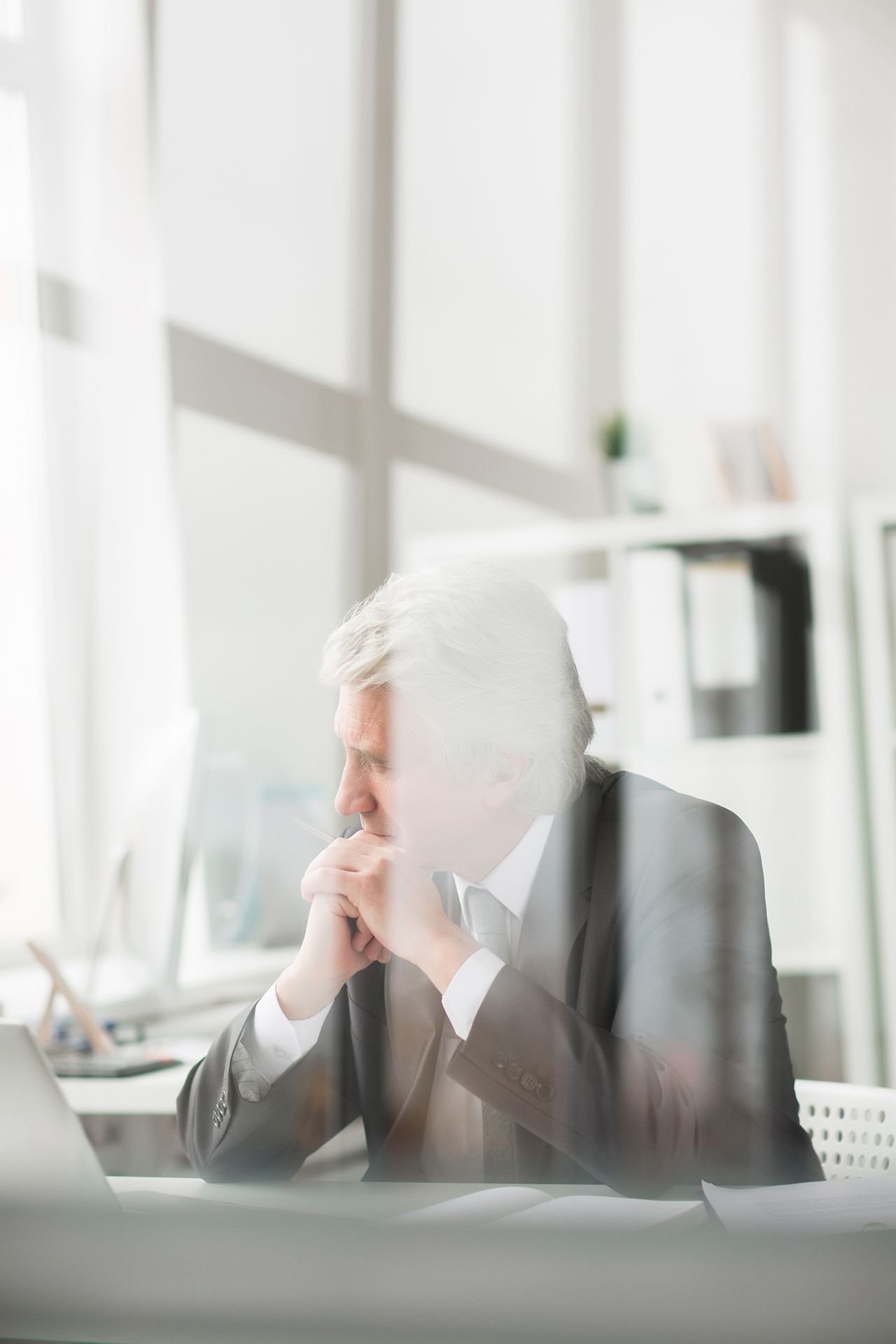 Pensive mature grey-haired businessman sitting by workplace in his office
