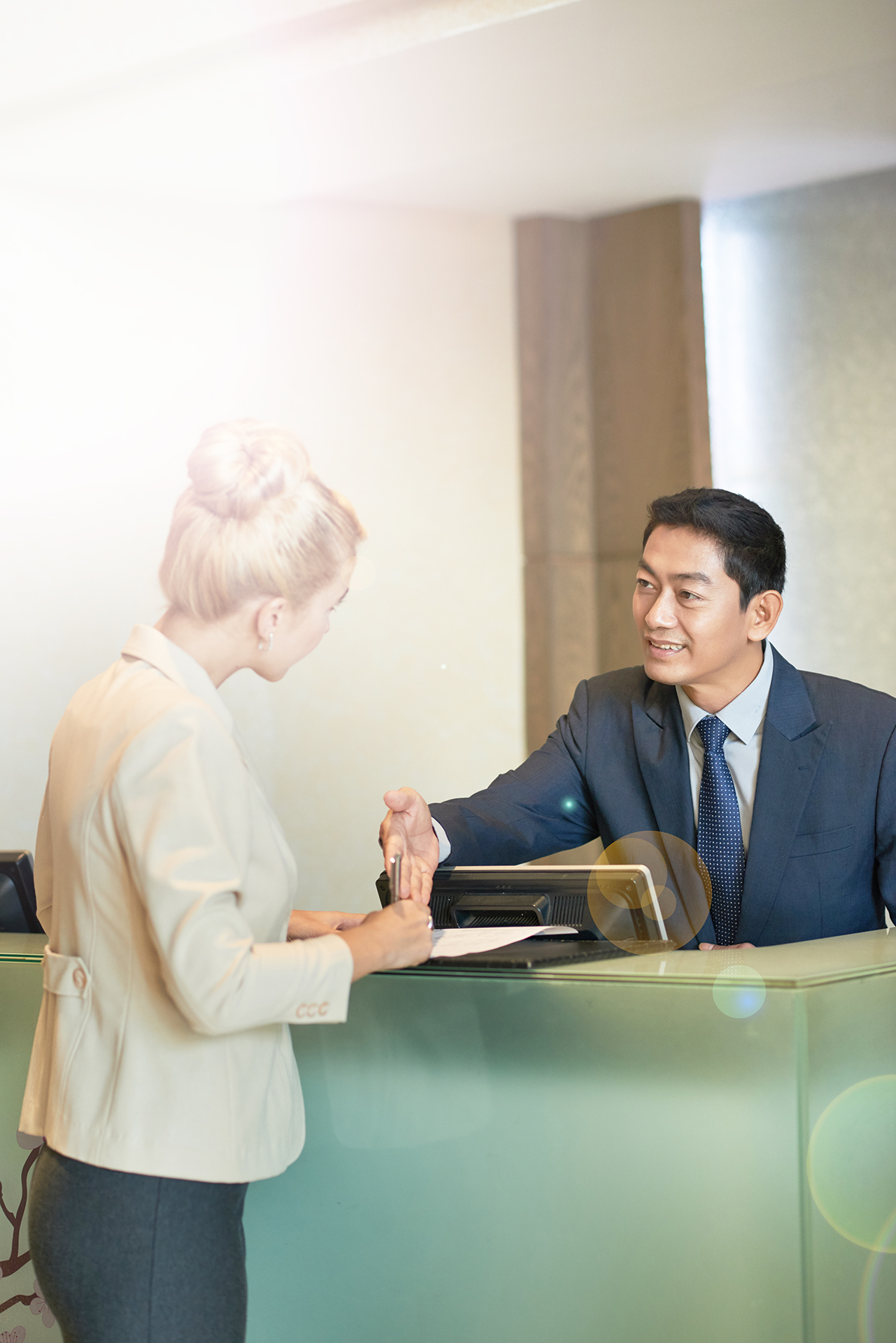 Business lady filling document on reception of hotel or office building